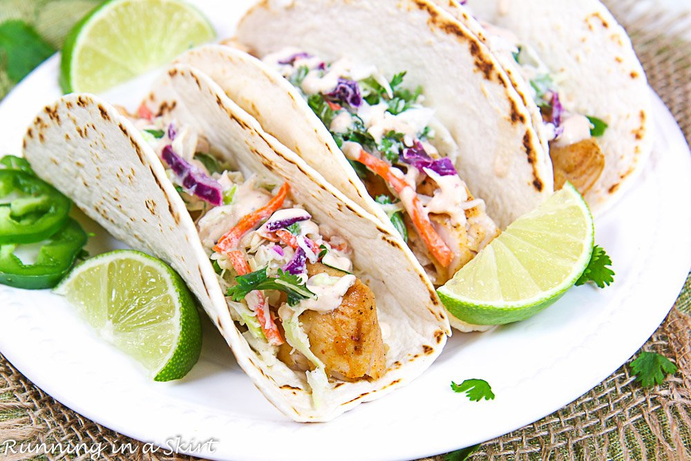 Close up of the fish tacos on a plate with a lime.