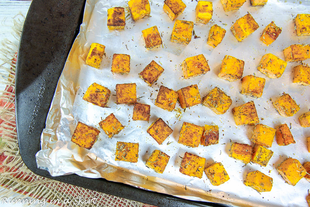 Cooked butternut squash on a baking sheet lined with foil.