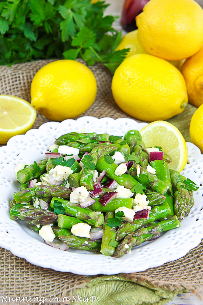 Cold Asparagus Salad on a white plate with lemon and parsley in the background.