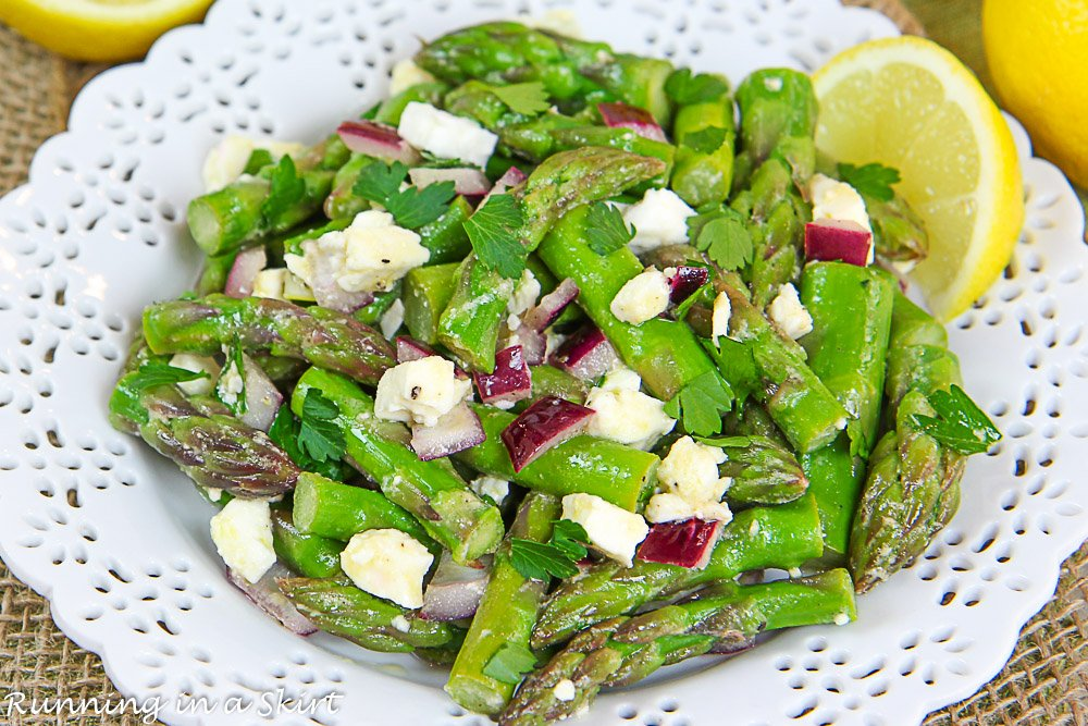 Asparagus Salad on white plate with feta and lemon.