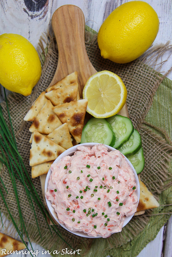 Overhead shot of Healthy Salmon Dip with crackers, cucumbers and lemon on a wood cutting board.