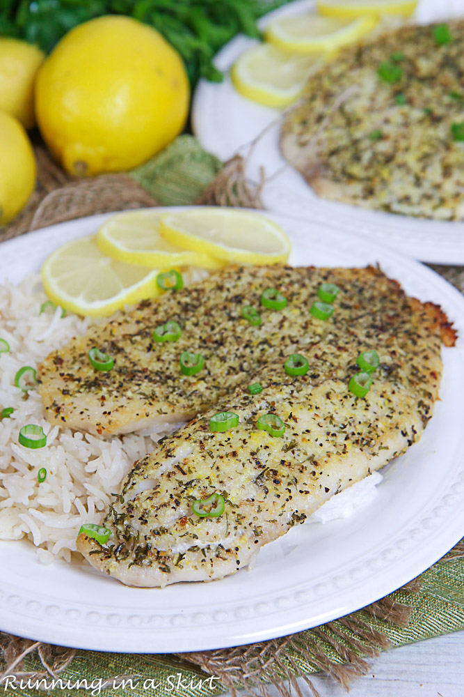 Lemon Pepper Tilapia on a white plate with rice and lemon.
