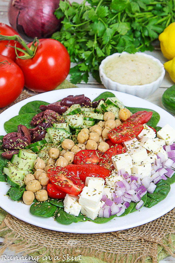 Mediterranean Chopped Salad on a white plate with the dressing in the background.