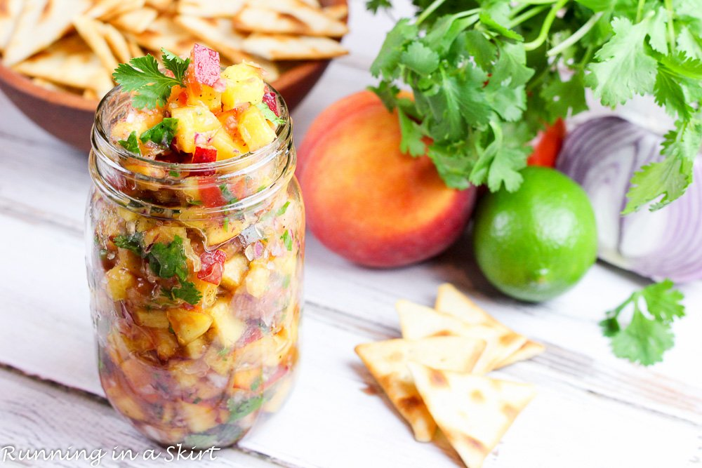 Fresh Peach Salsa recipe in a jar with peaches, lime, cilantro and chips in the background.