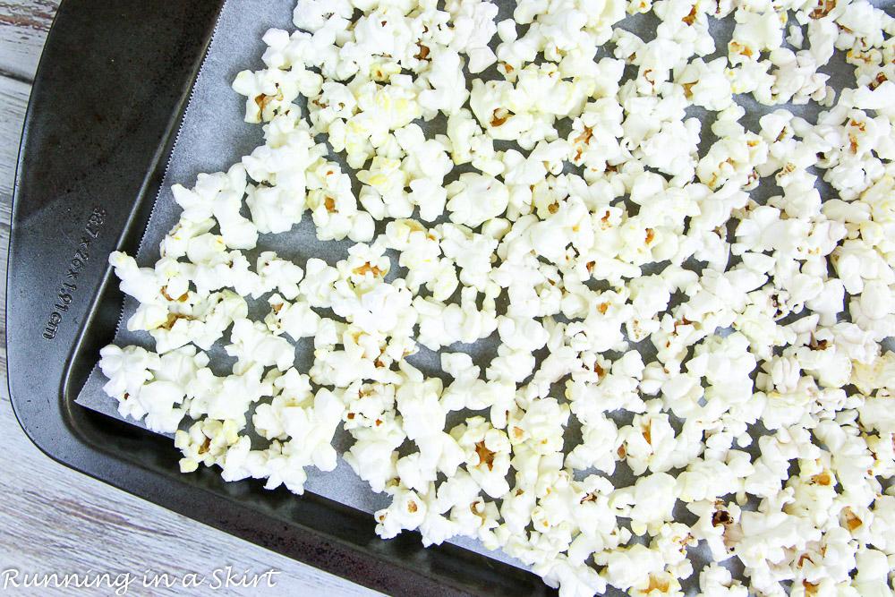 Plain popcorn on a baking sheet.