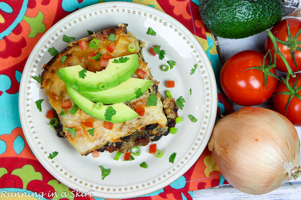 Crock Pot Vegetarian Enchilada Casserole on a white plate topped with garnishes.