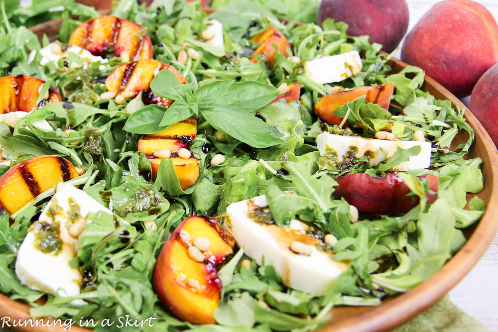 Caprese Grilled Peach Salad recipe on a plate with peaches in the background.