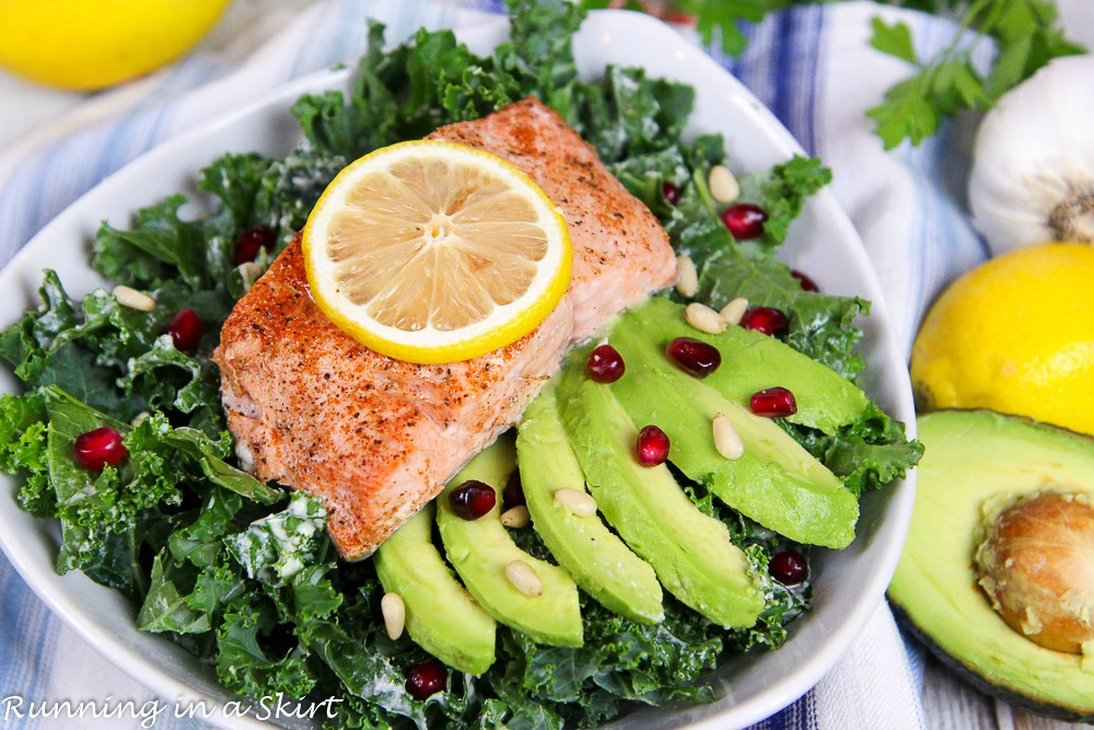 Baked Salmon Kale Salad with Tahini Dressing in a white bowl.