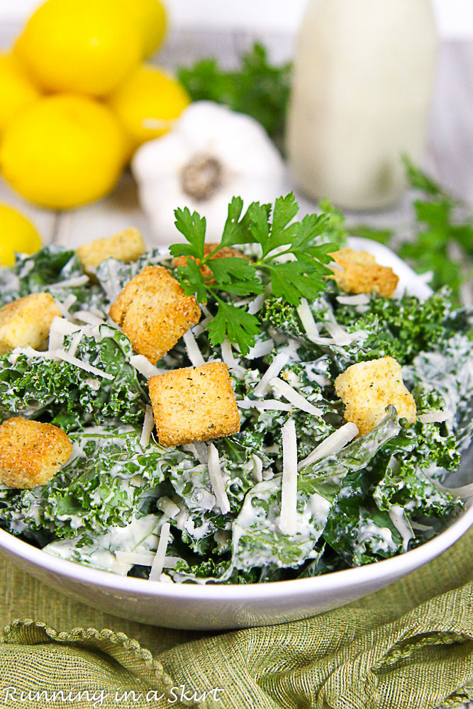 Kale Caesar Salad in a white bowl with lemon and garlic in the background.