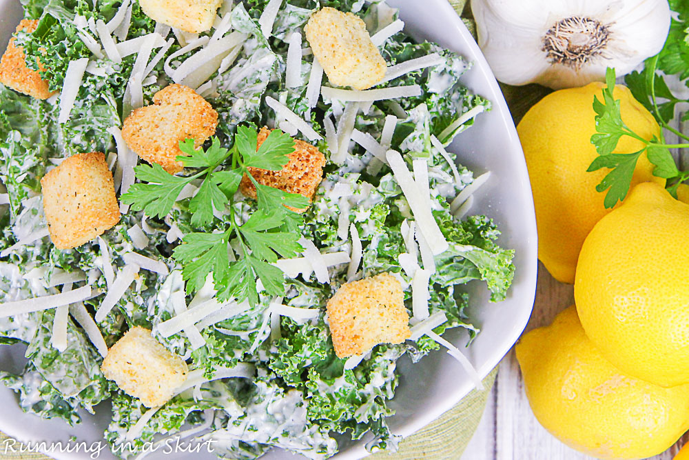 Overhead shot of the Kale Caesar Salad and dressing with lemons.