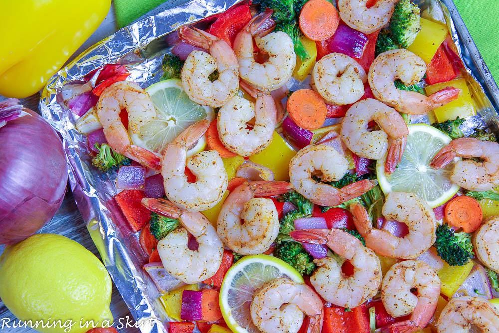 Shrimp, vegetables and lemons on a pan.