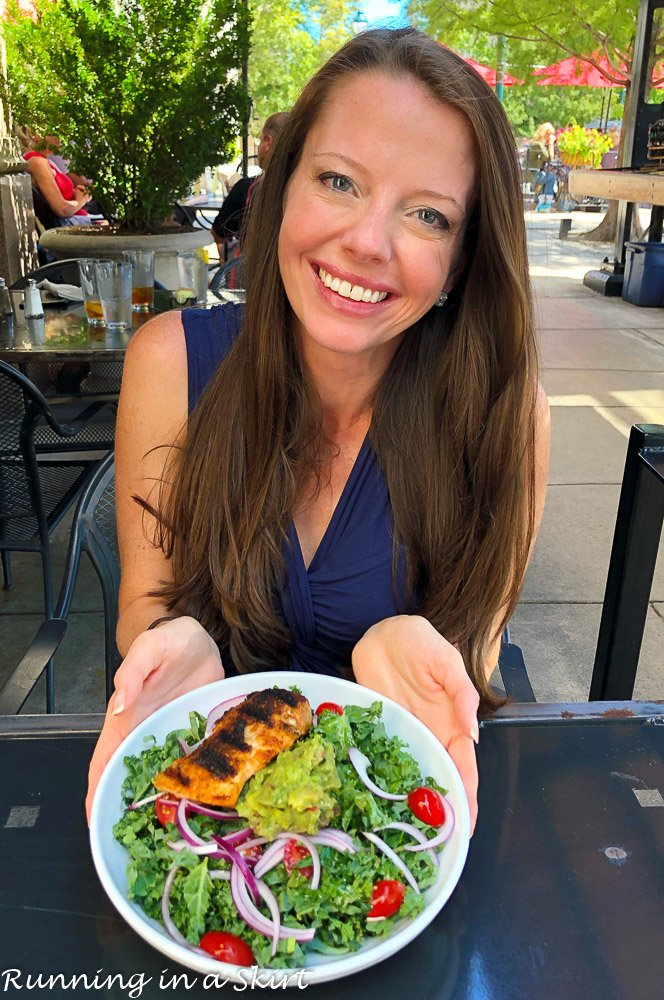 Girl holding a plate with a salmon salad.