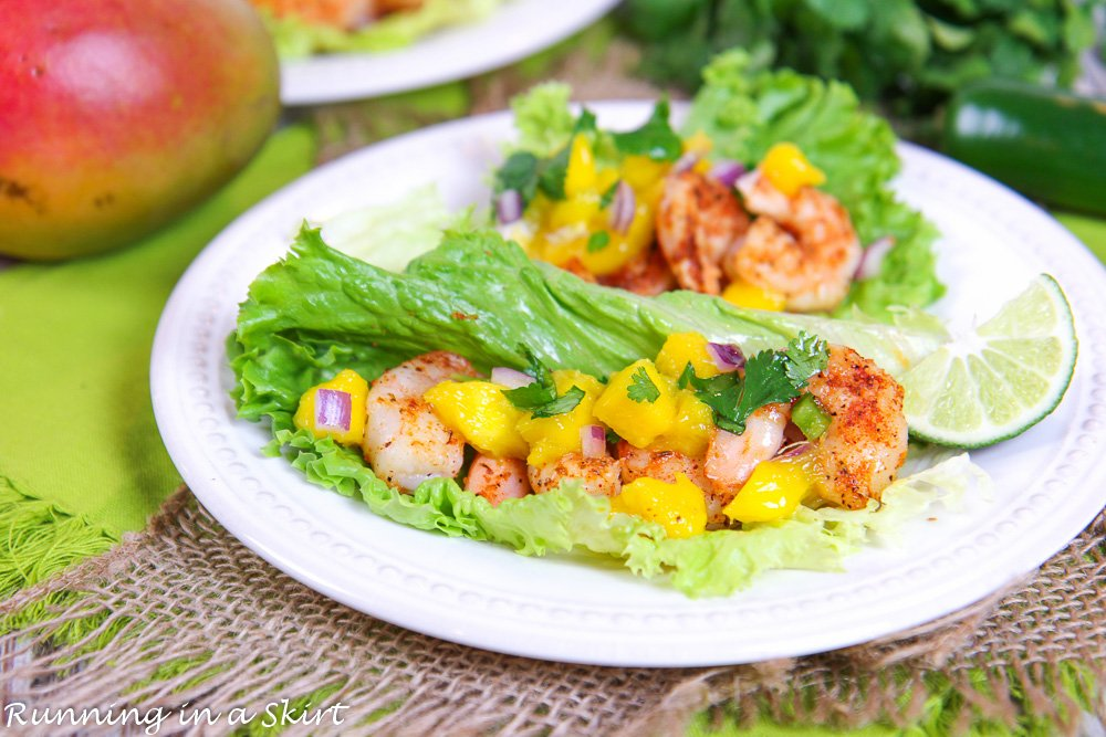 Lettuce Wrap Shrimp Tacos on white plate with lime and mango in the background.