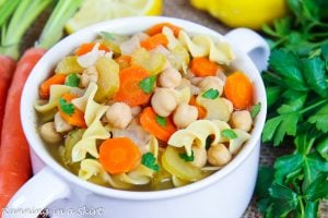 Closeup of soup with chickpeas, carrots, celery, onions and garlic.