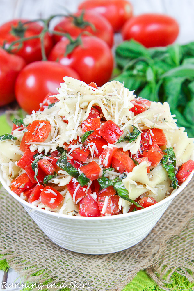Bruschetta Pasta Salad recipe in a bowl with tomato and basil.