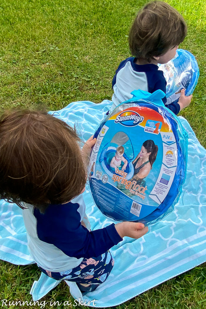 Twin toddlers holding SwimWays Toddler Spring Floats