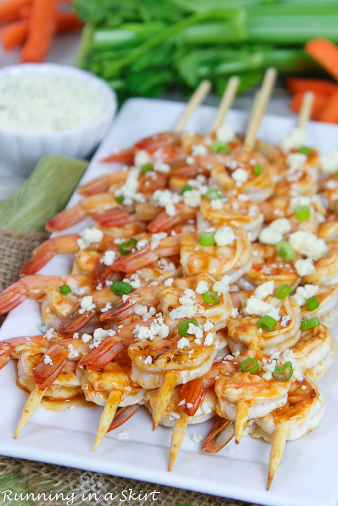 Shrimp on a white plate with celery and carrots.