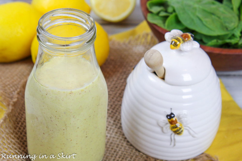 Healthy salad dressing in glass bottle next to honey pot.