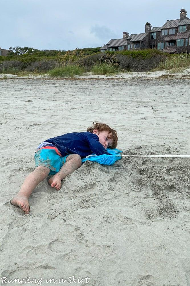 Toddler laying on sand Kiawah Island beaches.