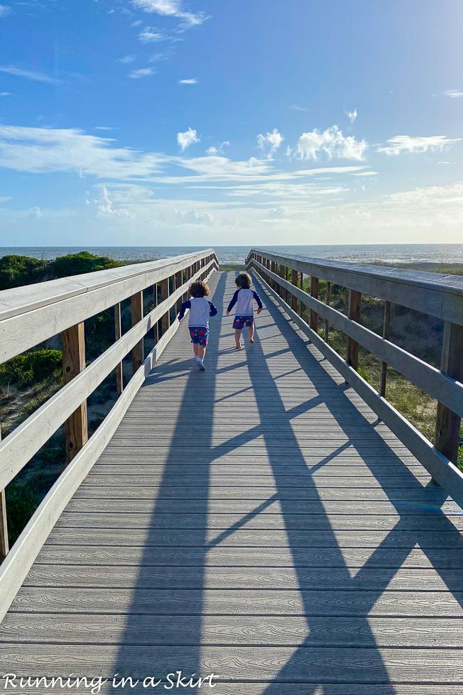 Toddlers running on beach boardwalk.