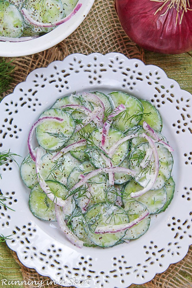 Overhead shot of Creamy Cucumber Dill Salad on a plate with a serving bowl.