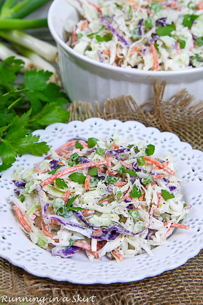 Healthy Coleslaw on a white plate with a serving bowl in the background.