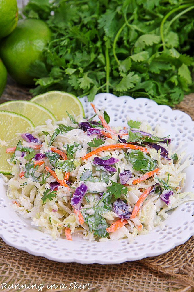 Finished product of the slaw with limes and cilantro in the background.