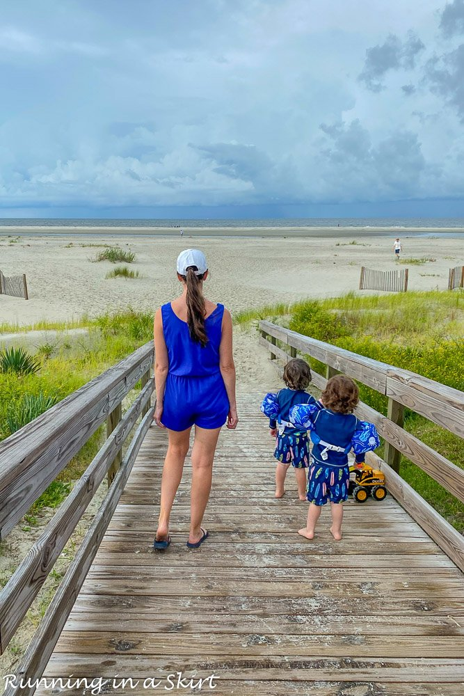 Mom walking with toddlers to the beach.